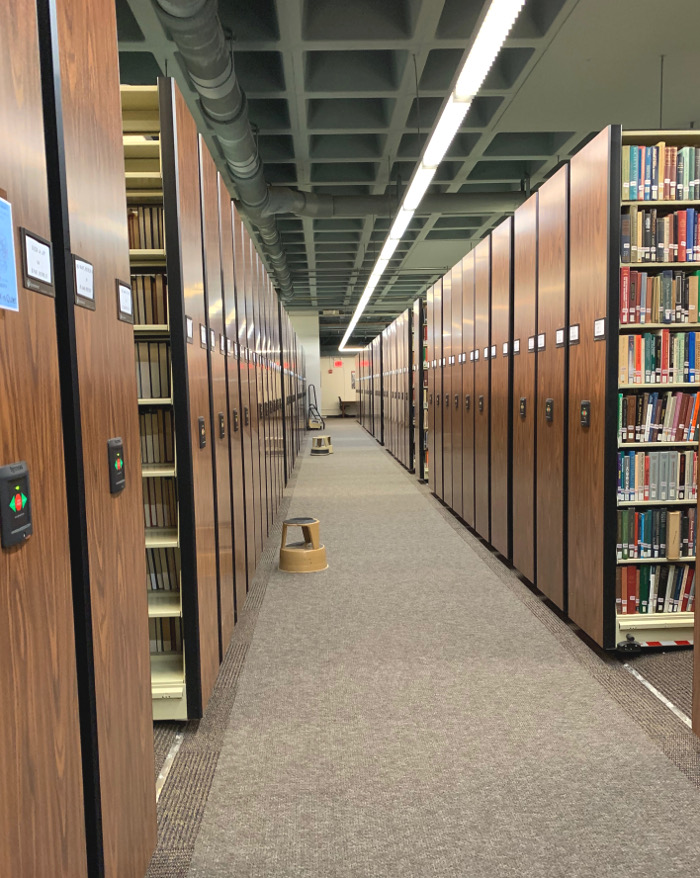 An aisle between two long rows of bookshelves.