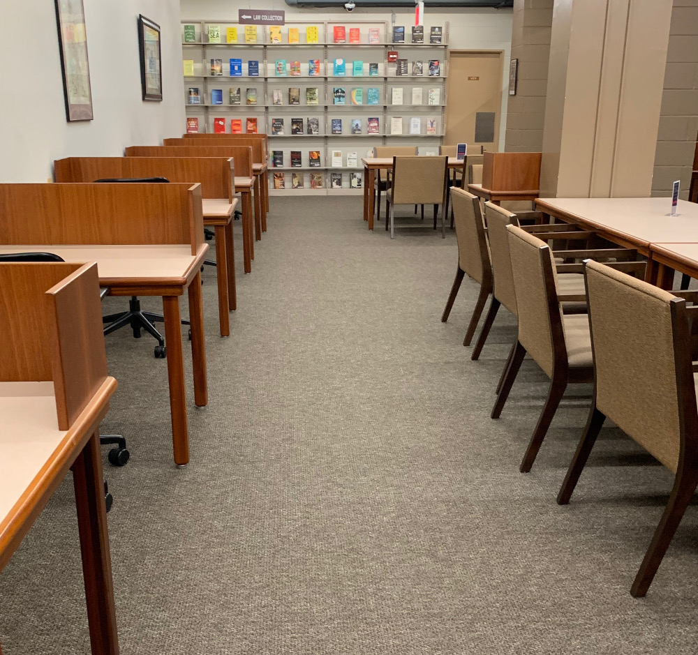 To the left are a row of individual study carrels. To the right are beige desk chairs lining a rectangular table. In the background, there is a bookshelf with colorful books facing outward.