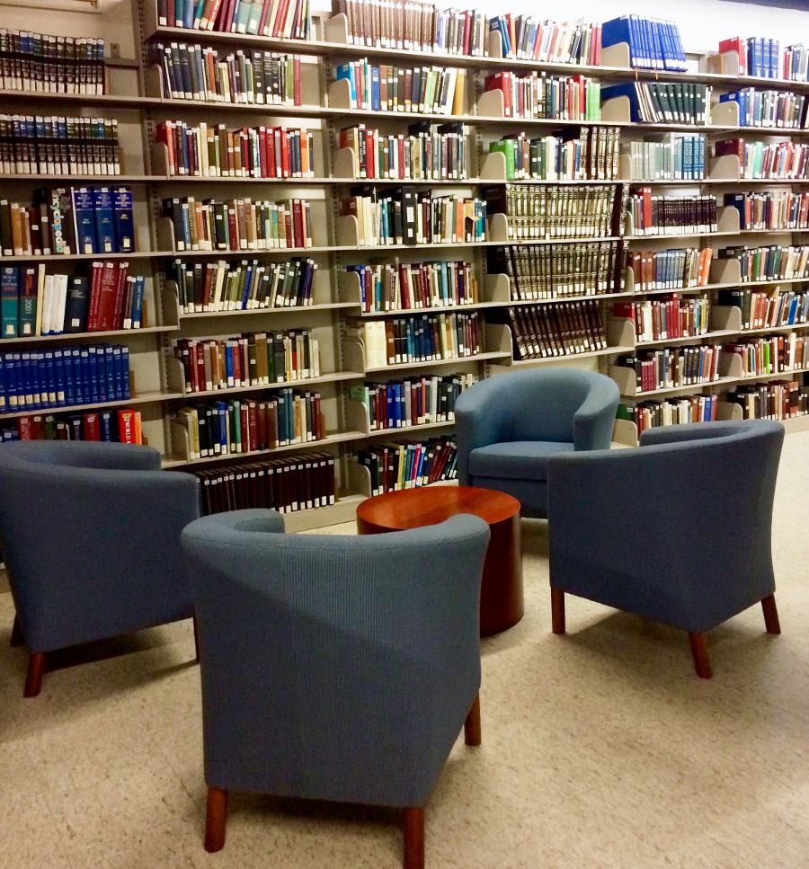Four blue armchairs surround a short, wooden, circular table. Full bookshelves are in the background.