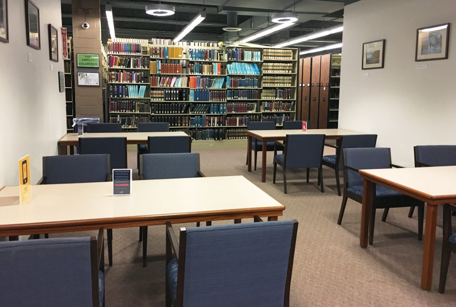 A room with four rectangular tables, each with four blue desk chairs around it. A row of bookshelves is behind the tables.