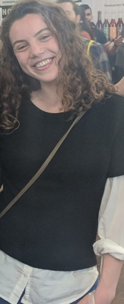 A smiling woman with shoulder-length, curly brown hair wearing a black and white shirt.