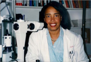 Dr. Patricia bath wearing a lab coat and sitting beside an eye examination instrument.