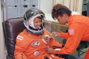 Two African-American women. One woman, Mae Jemison, is sitting wearing a space suit and helmet, smiling at the camera. The second woman, Sharon McDougle, is helping prepare Mae's space suit.