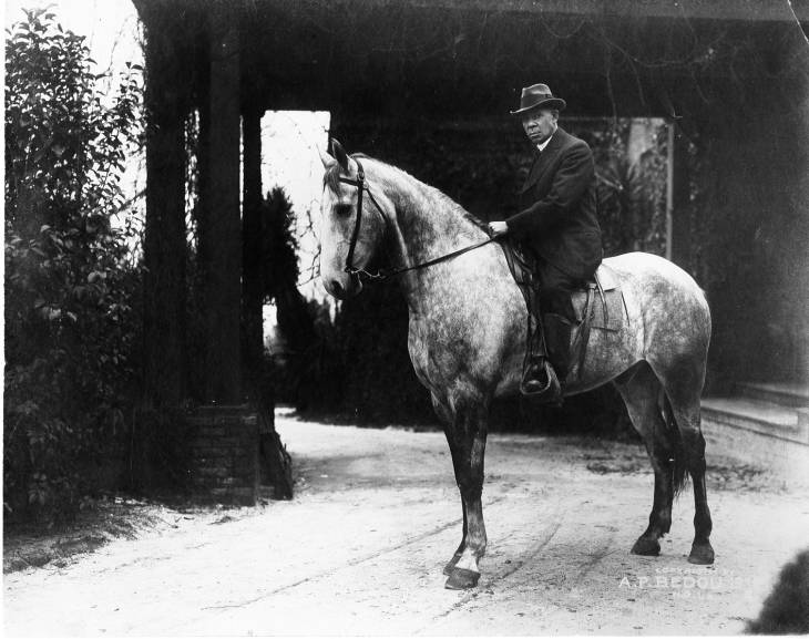 Booker T. Washington riding a flea bitten grey horse