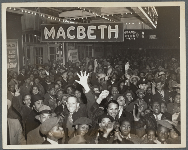 Large crowd under a theater awning with a large sign above them that says Macbeth