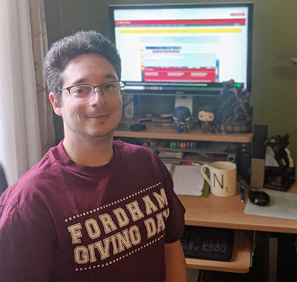 A man wearing glasses and a maroon Fordham t-shirt sits in front of a desktop computer.