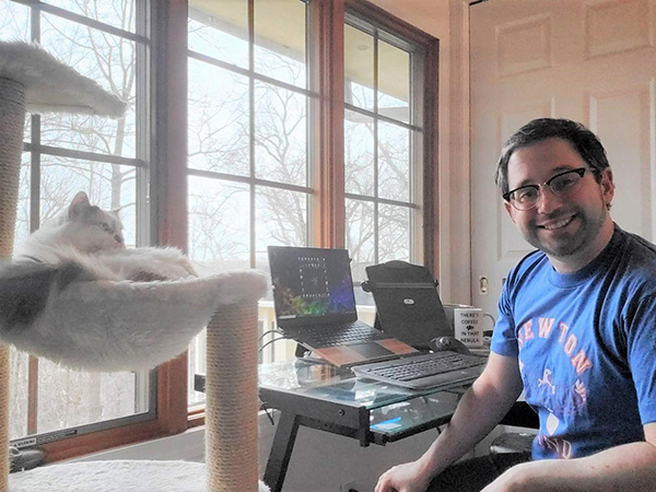 A man wearing glasses sits in front of a laptop. A fluffy white and gray cat lays in a cat tower to his left.