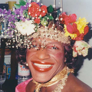 A woman smiling and wearing a hat covered in flowers.