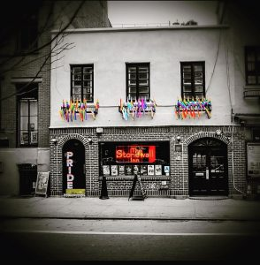 The storefront of the Stonewall Inn decorated with rainbow flags.