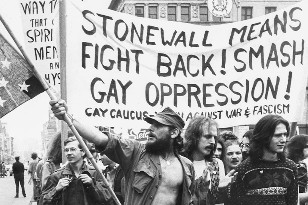 Protestors marching through the street holding signs during the Stonewall Riot.