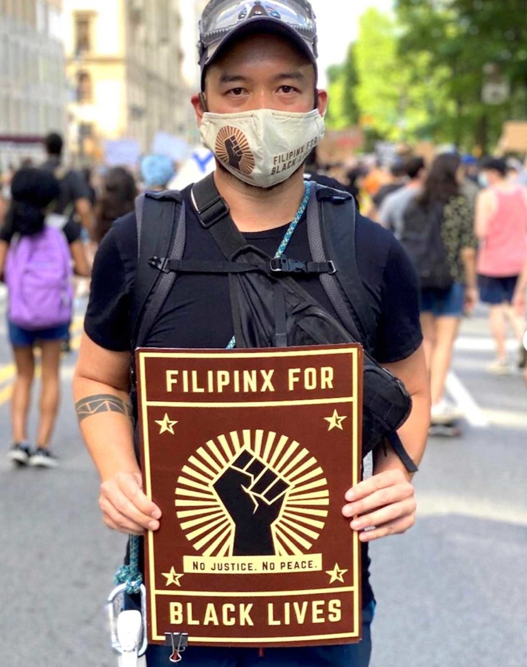 """A man wearing a face mask stands in front of a crowd during a protest. He is holding a poster with an image of a closed fist and the words """"Filipinx for Black Lives"""" across the top and bottom of the poster. Under the image of the fist are the words """"no justice, no peace."""""""