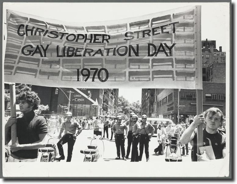 """Two men at a march holding a banner that reads, """"Christopher Street Gay Liberation Day 1970."""" Behind them, police officers stand in the street."""