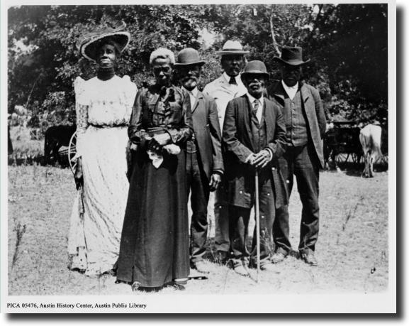 A black and white photo of a group of six African American men and women dressed in formal attire, standing in front of trees and looking into the camera.