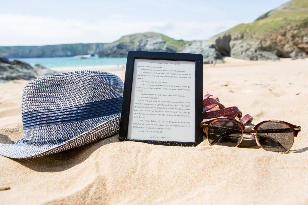A hat, e-reader, and pair of sunglasses in the sand at the beach, with the ocean in the background.