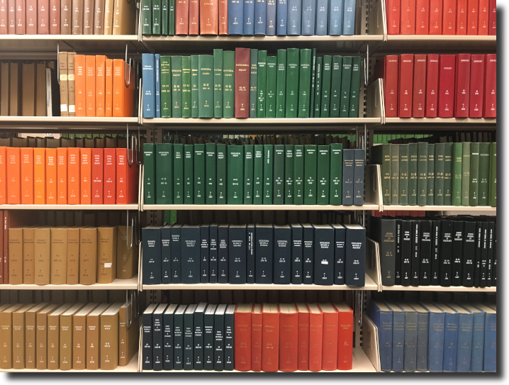 Bookshelves filled with periodicals in colorful bindings.