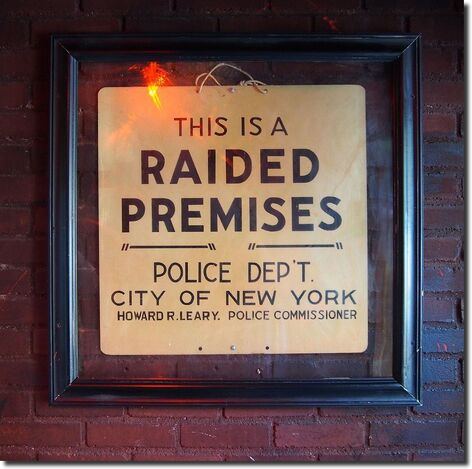 """A framed sign on a brick wall that reads, """"This is a raided premises. Police Dep't. City of New York. Howard R. Leary, Police Commissioner."""""""